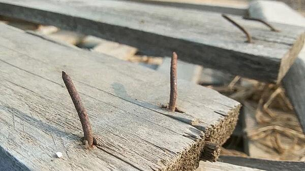 nail sticking out of a wooden board